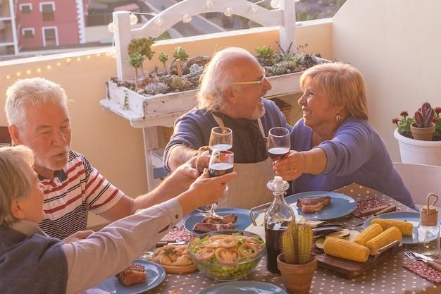 Веселые две пожилые пары празднуют вместе, поджаривая бокал вина на вечеринке на террасе. пожилые люди веселятся за ужином на крыше. пожилые люди едят и напитки на вечеринке на террасе