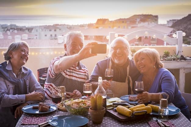 Веселые две пожилые пары обедают на вечеринке на террасе и делают селфи с помощью смартфона пожилые люди