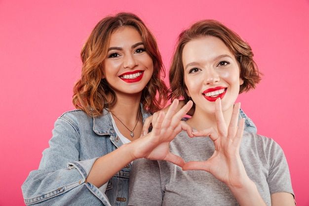 Cheerful two women hugging showing heart love gesture.