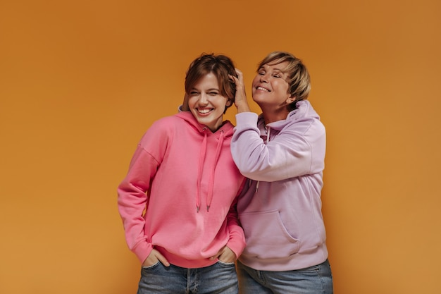 Веселые две женщины с короткими волосами в широких стильных толстовках и крутых джинсах улыбаются и веселятся на оранжевом изолированном фоне.