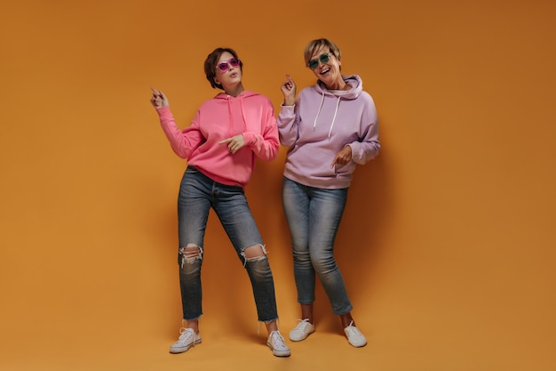 Cheerful two women with short hairstyle in cool sunglasses in stylish hoodies and skinny jeans dancing on orange isolated background.