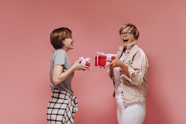 Веселые две женщины с короткой современной прической в стильной одежде и очках держат красные подарочные коробки и радуются на розовом фоне.