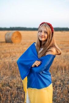 농업 분야에서 우크라이나의 국기에 싸여 쾌활한 우크라이나어 소녀