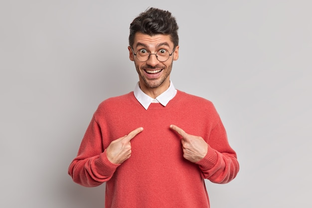 Cheerful unshaven caucasian adult man points at himself smiles broadly