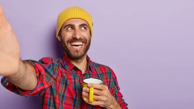 Cheerful unshaven male student enjoys hot drink from yellow mug, takes selfie, keeps arm outstretched, smiles positively, wears yellow hat and checkered shirt