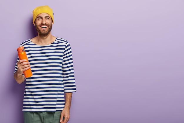 쾌활한 형태가 이루어지지 않은 밀레 니얼 남자는 뜨거운 음료와 함께 플라스크를 들고, 노란 모자와 줄무늬 점퍼를 착용하고, 기분이 좋고, 보라색 배경에 서서, 프로모션 콘텐츠를위한 공간을 복사합니다.