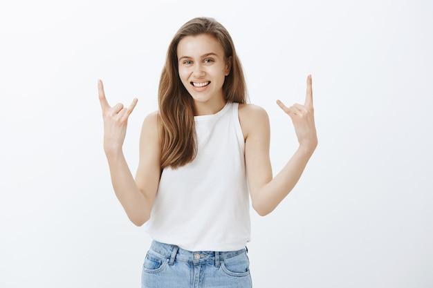 ロックンロールのジェスチャーを示し、楽しんで、コンサートを楽しむ陽気な陽気なブロンドの女の子