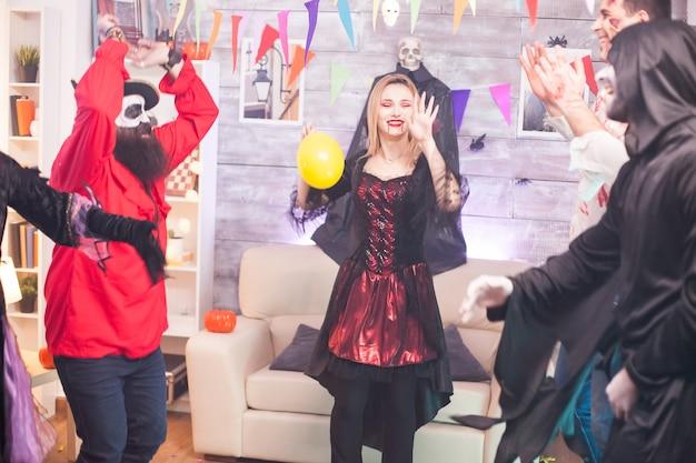 ハロウィーンのお祝いに手を上げて踊る血まみれの唇を持つ陽気な吸血鬼の女性。