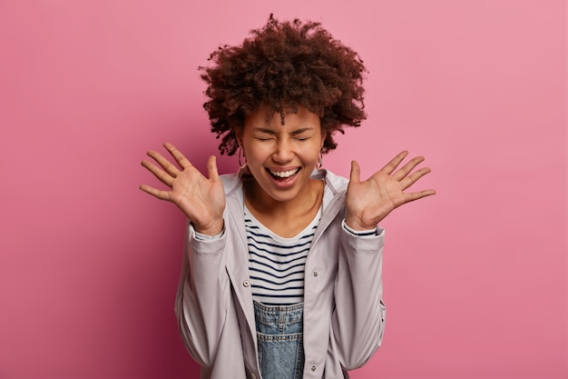 Веселая, очень счастливая женщина поднимает ладони и смеется, не может перестать хихикать, закрывает глаза, радуется очень позитивным новостям, находясь на девятом облаке, одета в куртку, со смешным выражением лица, изолирована на розовом