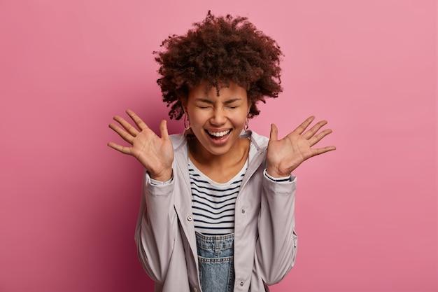 Una donna allegra e molto felice alza i palmi e ride, non riesce a smettere di ridacchiare, chiude gli occhi, si rallegra di notizie molto positive, essendo al settimo cielo, vestita con una giacca, ha un'espressione divertente, isolata sul rosa