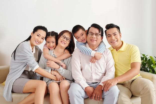 Веселые вьетнамские дети, родители, бабушки и дедушки сидят на диване в гостиной, обнимаются и смотрят в камеру