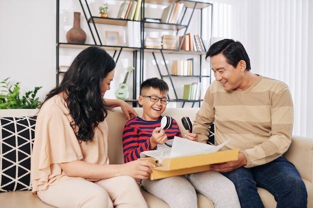 Cheerful vietnamese parents giving son big box with modern headphones inside for birthday