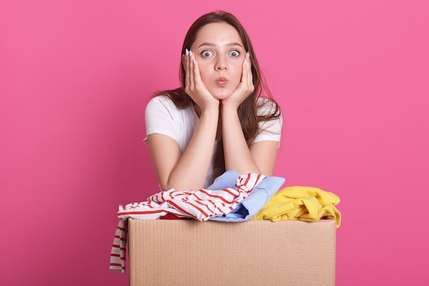 Cheerful volunteer standing isolated over pink, near box with donated clothes, young woman makes air kiss, looks directly at camera. charity concept.