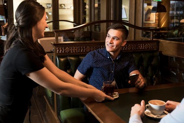 Веселая официантка, подающая чай красивому мужчине