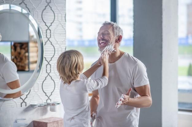 陽気な洗濯。朝、バスルームで父親のあごひげを白い石鹸の泡で塗る子供