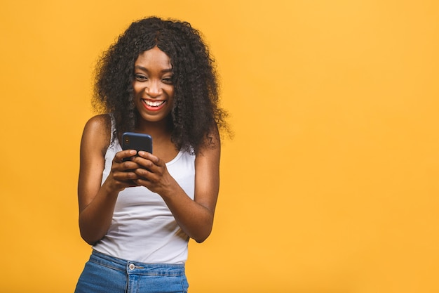 Cheerful wavy-haired african american black girl holding in hands phone chatting on web