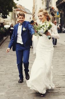 Cheerful wedding couple holds each other hands running on the pavement along the street