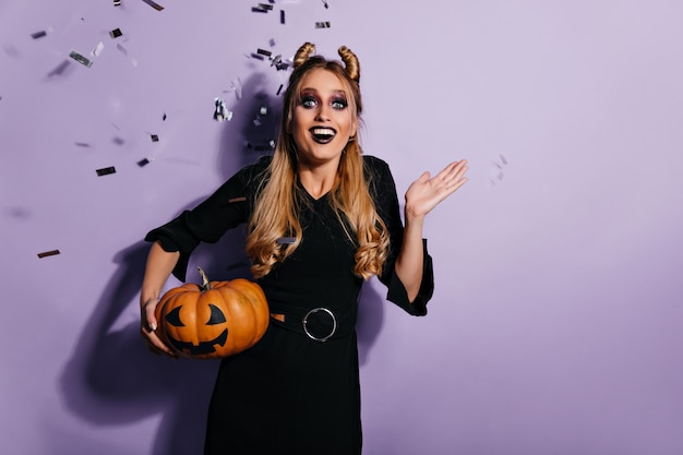 Cheerful well-dressed witch holding halloween pumpkin. emotional blonde vampire having fun at party.