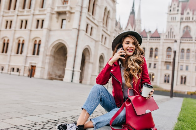Cheerful white female model in street outfit calling friend while sitting beside beautiful palace