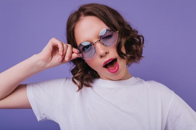 Веселая белая девушка в солнечных очках, игриво позирует на ярко-фиолетовой стене. внутреннее фото чувственной фигурной молодой женщины.