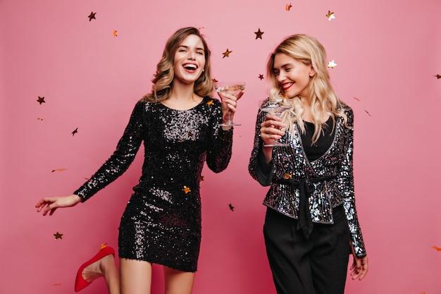 イベントを楽しんでいる短い輝きのドレスを着た陽気な白人女性。シャンパンを飲んでいる2人のうれしい女の子の屋内写真。