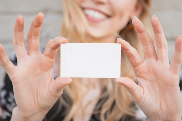Cheerful white woman showing an empty card