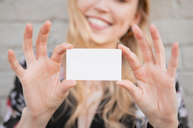 Cheerful white woman showing her business card