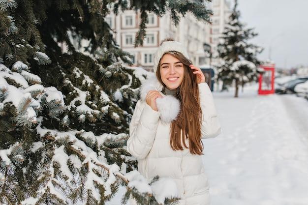 陽気な白人女性はニットの帽子と暖かいコートを着て、木の横で優しく笑顔でポーズします。冬の休日を屋外で楽しんでいる毛皮のジャケットに長い髪の恍惚とした女性モデル。