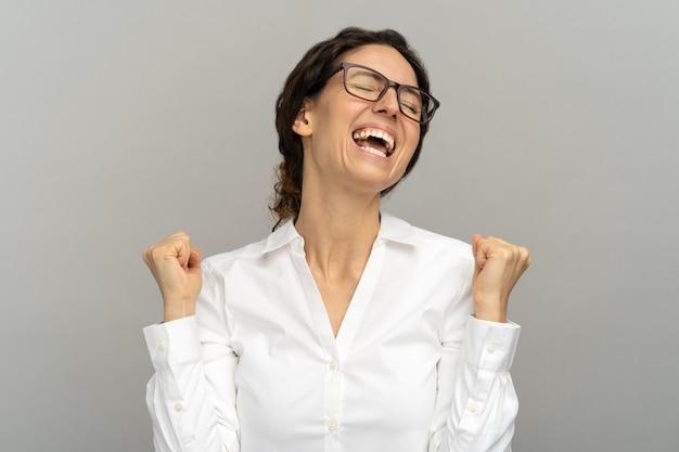 쾌활 한 성공적인 회사원 또는 주먹을 올리는 안경에 사업가 회색 배경에 고립 된 그녀의 목표를 달성하기 위해 행복 한 경력 사다리 승진 또는 보상을 기념합니다.