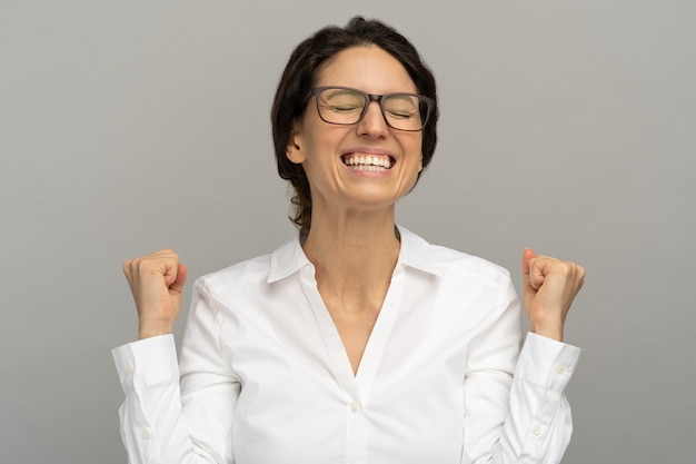 Cheerful winning successful office worker raising fists celebrates career ladder promotion or reward, being happy to achieve her aim