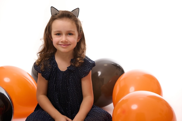 Cheerful winsome adorable little girl in black carnival dress and hoop with cat ears sitting on a white surface with bi colored balloons, smiles looking at camera. halloween decoration. copy space