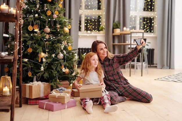 쾌활한 여자와 집에서 거실의 중심에 장식 된 크리스마스 트리로 셀카를 만드는 잠옷에 사랑스러운 어린 소녀