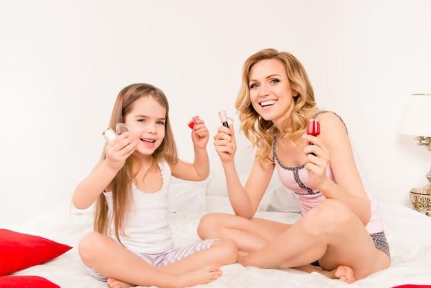 Веселая женщина и ее девочка-ребенок держат разные лаки для ногтей
