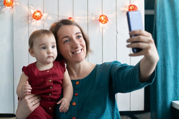 陽気な女性と彼女の小さな娘がクリスマスの飾りで自分撮りをしています。冬の休日のリモートお祝い、家にいるコンセプト。物語を作成する母ブロガー。