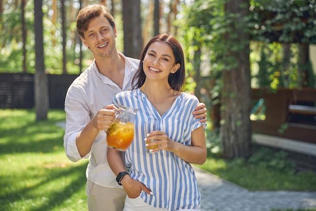 陽気な女性と成功した男性が写真カメラで見てポーズをとる