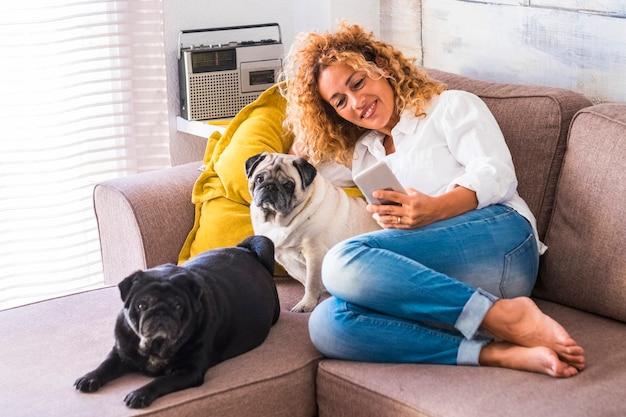 家にいる陽気な女性は、2人の親友の犬のパグを近くに置いてソファに座ります-動物のいる本当のライフスタイルの人々