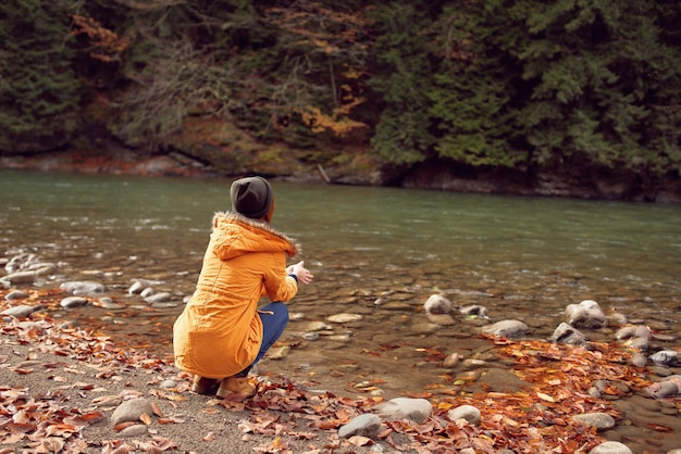 Cheerful woman in autumn clothes near forest river