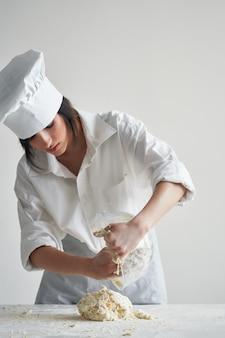 シェフの制服を着た陽気な女性のパン屋は、テーブルワークで生地を転がします