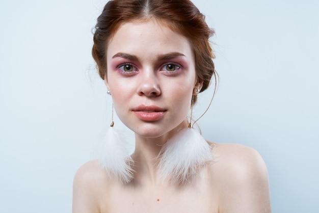 쾌활한 여자 벌거 벗은 어깨 무성한 귀걸이 화장품 보석. 고품질 사진