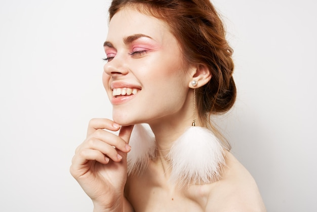 Cheerful woman bare shoulders fluffy earrings cosmetics jewelry