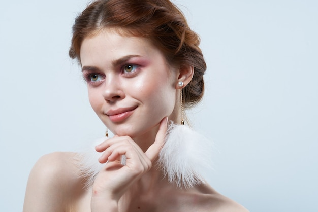Веселая женщина с открытыми плечами пушистые серьги косметика украшения