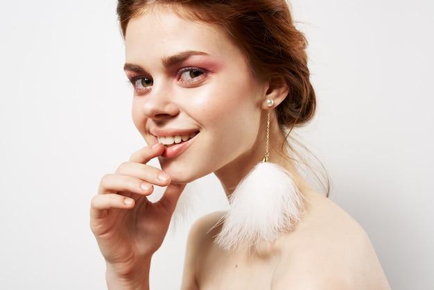 Веселая женщина голые плечи пушистые серьги студии обрезанный вид. фото высокого качества