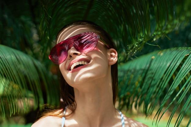 陽気な女性の裸の肩の緑の葉エキゾチックな熱帯