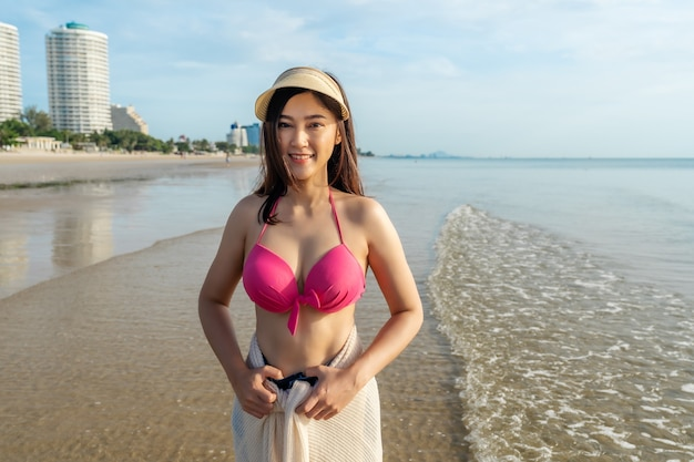 Cheerful woman in bikini standing at the sea beach