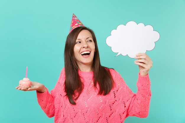 Cheerful woman in birthday hat looking up, hold cake with candle, empty blank say cloud speech bubble for promotional content isolated on blue background. people lifestyle concept. mock up copy space.