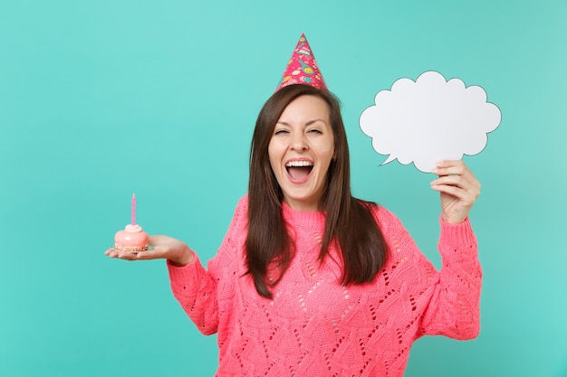 Cheerful woman in birthday hat screaming, hold cake with candle, empty blank say cloud, speech bubble for promotional content isolated on blue background. people lifestyle concept. mock up copy space.