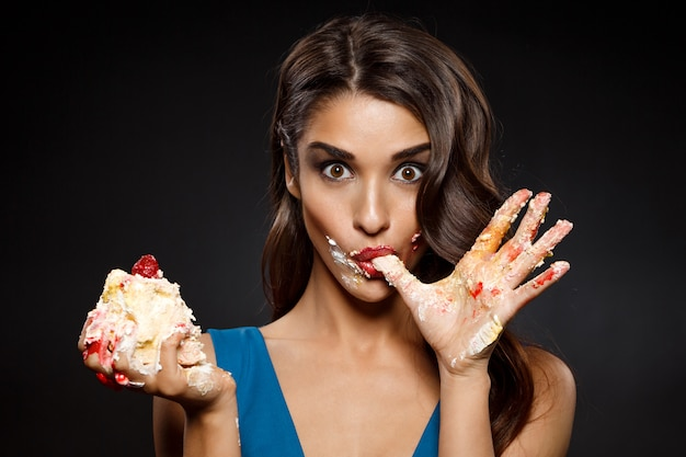 Cheerful woman in blue dress eating piece of cake