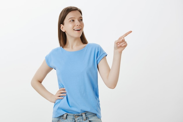 Cheerful woman in blue t-shirt pointing upper right corner, showing your logo
