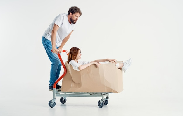 Cheerful woman in a box on a cargo trolley and energetic courier in jeans and a t-shirt
