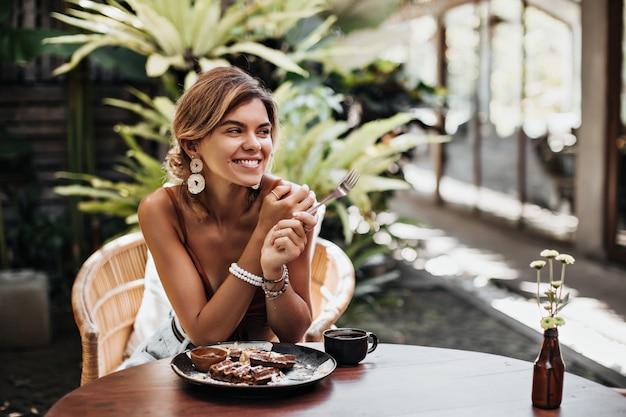 La donna allegra in reggiseno marrone e grandi orecchini bianchi sorride ampiamente e riposa in un caffè di strada in estate